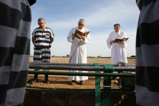 Two priests and inmates perform burial duty at Whitetanks cemetery, near Phoenix.
