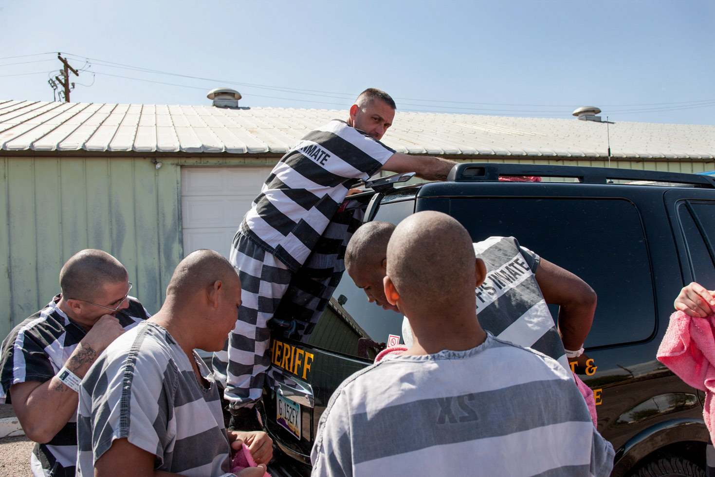 An inmate looks toward the camera as he cleans the guard's SUV.