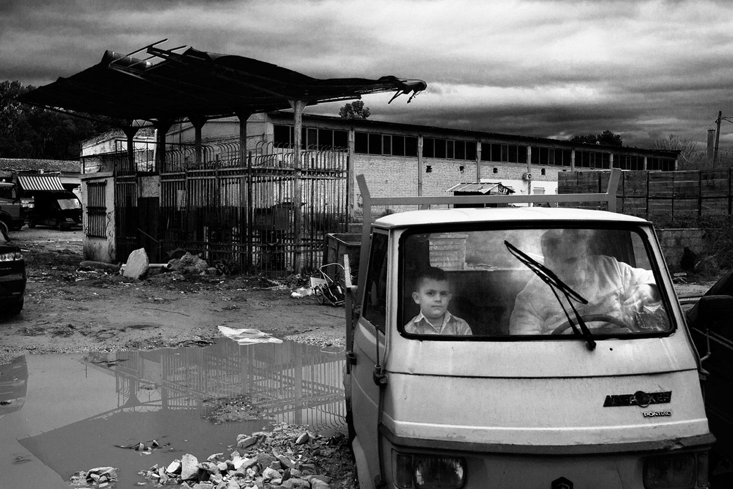 A boy accompanies his father to work.  Tirana, Albania, 2012