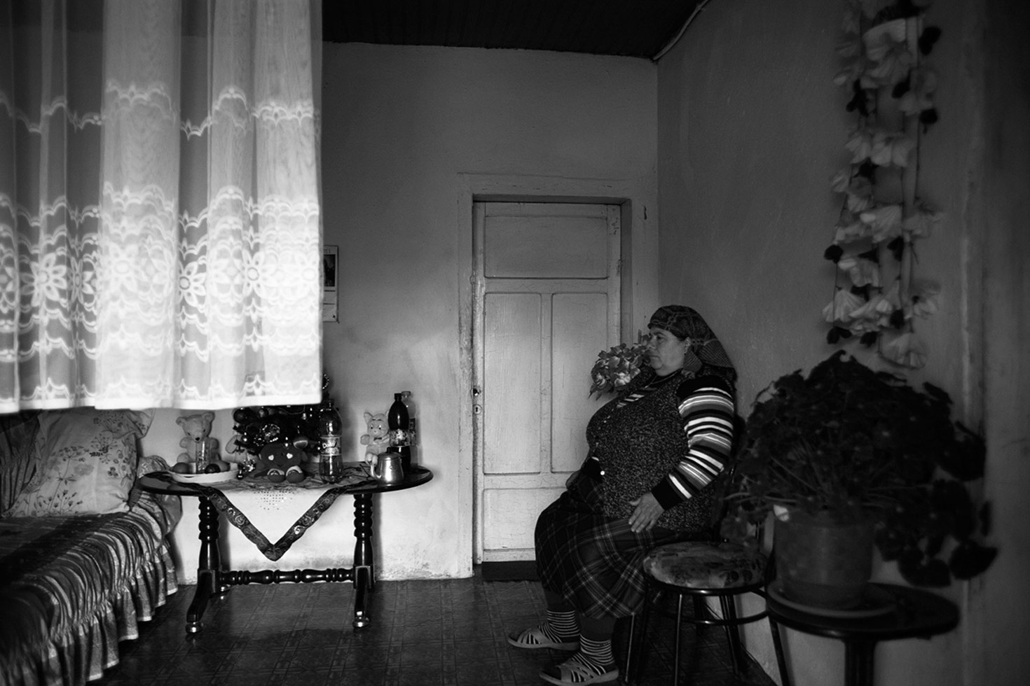 A woman living alone in her house. All the men of the family have fled to safety - they are targets of a 'Gjakmarrja,' a blood feud. The Kanun, a set of traditional Albanian laws, which has a powerful hold in this area, stipulates that only men can be killed, so the woman is safe.  Shkoder, Albania, 2012