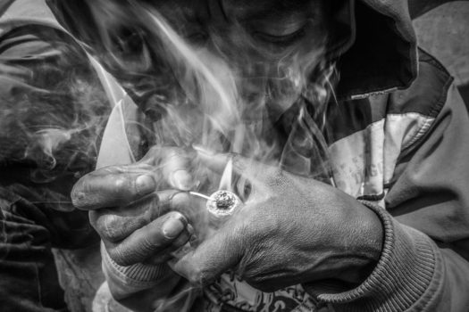 A woman on the street smokes bazuko or 'little devil', a cheap form of crack. 