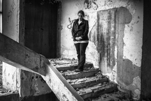 Sarajevo siege survivor Tanya Kresnjo in a bombed-out building stairwell.  Bosnia and Herzegovina.