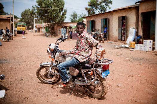 Portrait of 'Ibou,' a motorcycle taxi driver in Maliville in the Fouta Djallon highlands of Guinea. He makes the arduous 60 km, 10 hour ride down the steep, rock-strewn paths of Fouta to Senegal, up to three times a week. The Guinean roads are reported as being some of the worst in the world.
