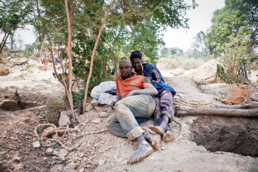 A two man team of migrant miners from Guinea relax next to their mine shaft in Senegal. Each takes it in turns to go down the 10 meter shaft for up to one hour at a time to extract gold-bearing rocks.