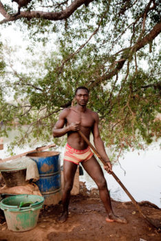 A migrant worker from Guinea with the shovel he uses to excavate sand from the River Gambia in Senegal. The sand will be washed and mixed with mercury to extract gold.