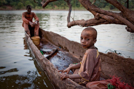 A young mine worker waits to be ferried across the River Gambia after working with his father at one of eastern Senegal's artisanal gold mines.
