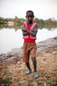 A young boy poses next to River Gambia at Diagabu Tenda.