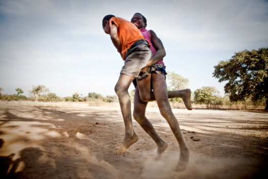 Young boys wrestling in a traditional Gambian style in the riverside village of Karantaba.