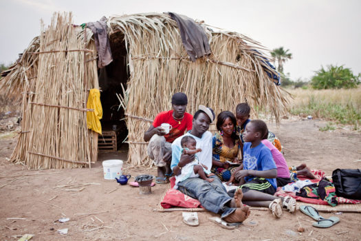 A migrant fisherman from Senegal with his family outside their seasonal fishing hut at Carrol's Wharf, The Gambia.