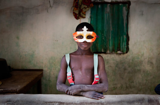 A young boy plays 'dress-up' with a Mardi Gras-style masque in the village of Mandinari, a populous settlement on a 'bolon' (tributary) off the River Gambia.