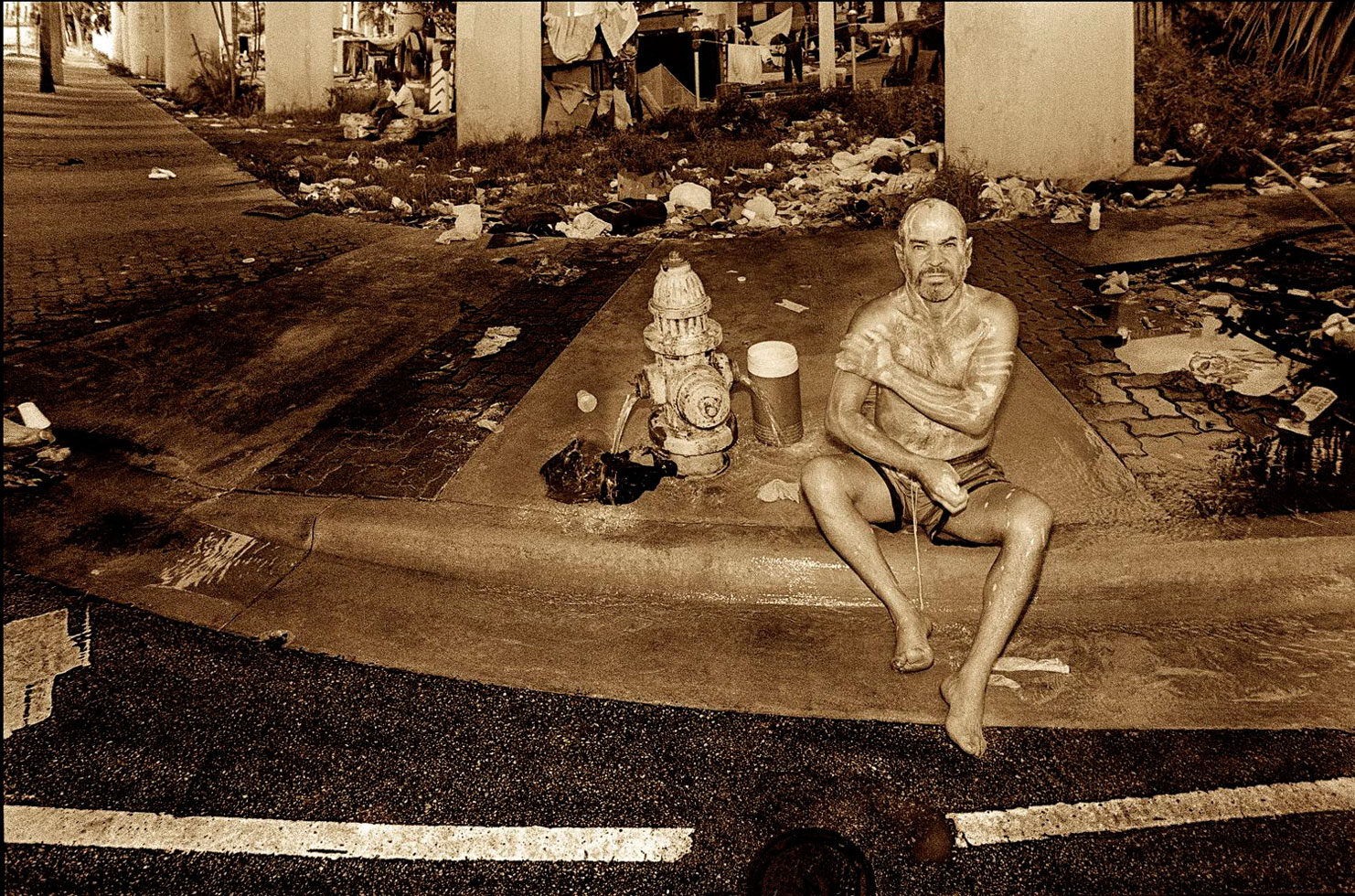 """Downtown Miami, Florida, 1993-1994.   While the city of Miami was being sued in the 1990's for violating the civil rights of homeless people, a judge ordered """"safe zones"""" be established where people could live without fear of arrest. In the photo a man is bathing at a water hydrant in Downtown Miami. This water source also served for drinking water and washing clothes."""