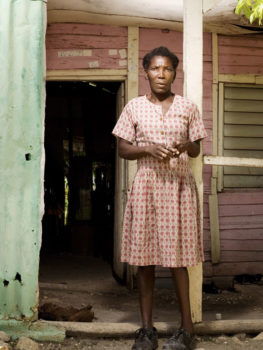 """Altagracia, """"Ta ta,"""" lives in this house with two of her three children. Three years ago, she joined a Christian church for the sole reason of being provided free rice every week for her family."""