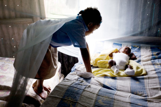 """Aida Valdez, 6, looks at her two-month-old cousin, Samuel, who was born three months prematurely but is now a healthy, growing """"hombrecito"""" (little man). In Las Pajas, mosquito nets are considered a luxury that few can afford, but the nets are vital in controlling outbreaks of malaria and the infamous dengue fever."""