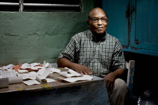 A few years ago, the sugar cane industry offered lifetime pensions to anyone who saved more than 350 pay-stubs during their working lives. Here, Chi Chi proudly shows some of the pay-stubs he saved. He was the only person in the Batey to have saved more than 350, which earned him and his wife, Sonia, a monthly pension of 2,985 pesos.