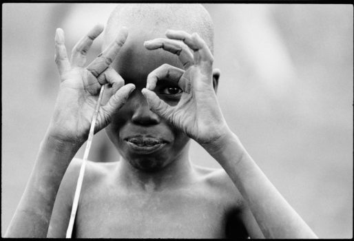 """Words and images from Betty Press.  """"When a child behaves like an adult he sees what an adult sees."""" African proverb  I was on assignment to document famine in war-torn southern Sudan. It was a very difficult time for the people but the children always made the best of the situation. This young boy cleverly got my attention by imitating me, the photographer.  Southern Sudan, 1993"""