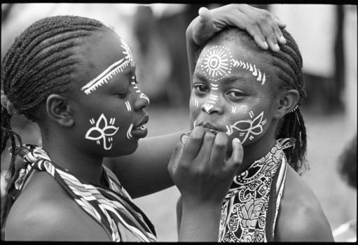 """""""She who spends time adorning herself knows she is going to dance."""" Kenyan proverb  Young dancers make up their faces in preparation for a dance. Many schools have extracurricular activities encouraging music, dance, and drama.  Kwangware Primary School Dancers, Nairobi, Kenya, 1990"""