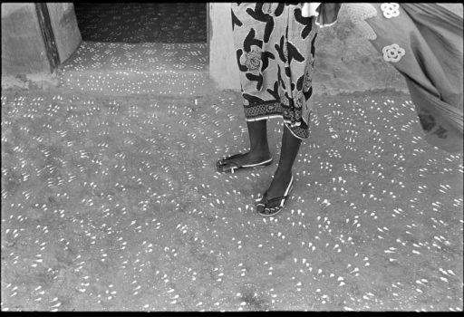 """""""The footprint of one person is narrow."""" Congolese proverb  Diafarabé, Mali, 1994  During the Peul Crossing of the Cattle Festival, the houses are cleaned, painted and decorated. This courtyard was decorated with a cat's-paw pattern created by three fingers dipped in whitewash."""