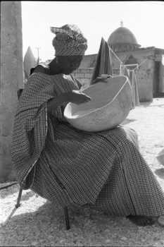 """""""A calabash with holes cannot be filled."""" Kenyan proverb  While visiting a women's group that was setting up a dried fish business, I saw this woman sitting in a courtyard cleaning rice. As she was doing this most mundane job, she was beautifully dressed and so composed that even having her picture taken did not distract her from her work.  Mbao, Senegal, 1988"""
