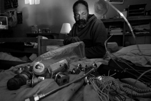 Mahir takes a moment to reflect as he works on disassembling door knobs for brass and metals. Because they do not have space to work on The Abdullahs frequently place the waste items they find and deconstruct from dumpsters and warehouses on their bed.