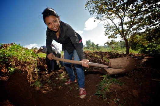 A young woman digs with a shovel, looking for gold ore that has been discarded by the large nearby mine. Low-grade ore that the large mine discards can be processed manually for a modest return.
