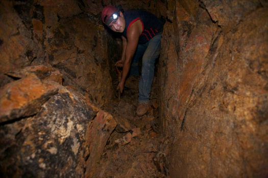 A young gold miner underground shovels gold ore in a tunnel. The small-scale miners have no equipment, it is forbidden by the terms of the concession to Canadian mining corporation 'B2 Gold' which allows only 1% of the mining to be done by small-scale miners.