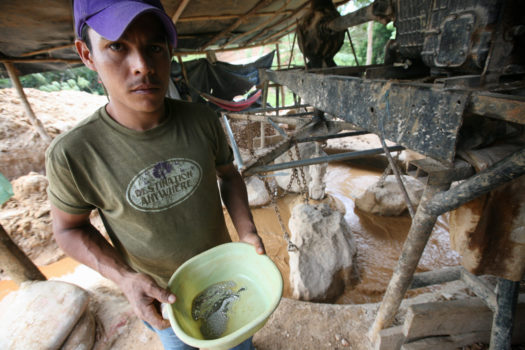 A miner holds a bowl with mercury near an 'arrastra' type gold mill.
