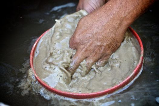 A miner washes away stone sediment to leave behind the mercury-gold amalgam.